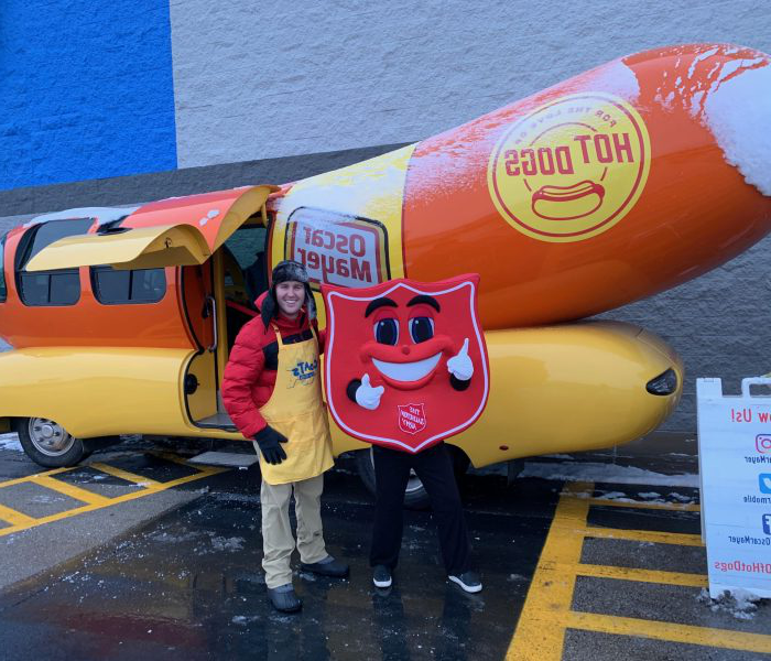 Tyler Peterson stands outside of the Weinermobile, a hotdog shaped bus.