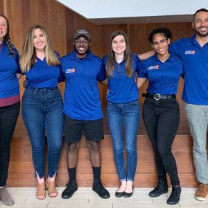 Xavier Balerdi, Sandra Rayo Orozco, Mikaela Medeiros, Vladimir Charles, Alyssa Forbess and Nicole Howe pose for a photo in their UF MBA blue polos.
