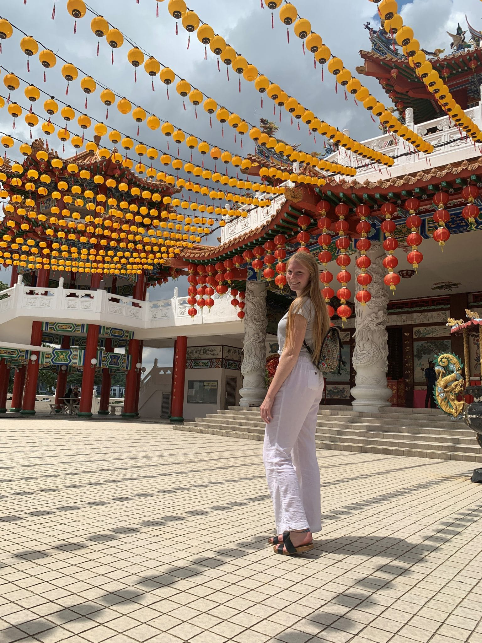 Chloe Beaver in Malaysia under an open roof filled with lanterns